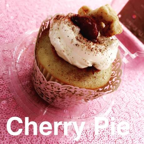 Vanilla cupcake with a cinnamon cherry pie filling and vanilla buttercream topped with a crust cookie and a cherry.